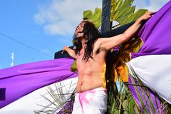 Homem não identificado que joga o papel, publicamente com referência a - decretando na rua da crucificação do ` s de jesus christ imagem de stock