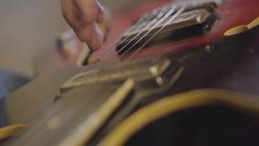 Homem não reconhecido da habilidade que joga as cordas de um close-up da guitarra vídeos de arquivo