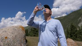 Homem na água potável do tampão da garrafa no fundo da montanha e do céu azul vídeos de arquivo