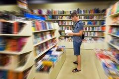 Homem na biblioteca que lê um livro Fotografia de Stock Royalty Free