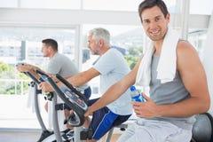Homem na bicicleta de exercício que guarda a garrafa de água foto de stock royalty free