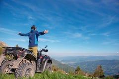 Homem na bicicleta do quadrilátero de ATV na estrada das montanhas Foto de Stock Royalty Free