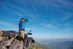 Homem na bicicleta do quadrilátero de ATV na estrada das montanhas Fotos de Stock Royalty Free