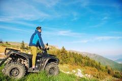 Homem na bicicleta do quadrilátero de ATV na estrada das montanhas Imagens de Stock