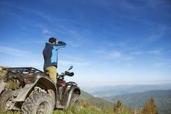 Homem na bicicleta do quadrilátero de ATV na estrada das montanhas Fotografia de Stock Royalty Free