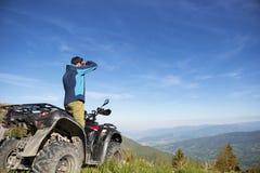 Homem na bicicleta do quadrilátero de ATV na estrada das montanhas Foto de Stock