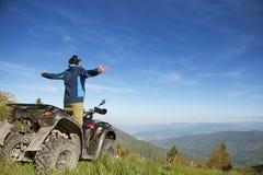 Homem na bicicleta do quadrilátero de ATV na estrada das montanhas Fotografia de Stock