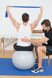 Homem na bola da ioga que trabalha com um fisioterapeuta Foto de Stock Royalty Free