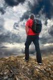 Homem na borda da montanha Turista na borda da montanha e no céu escuro Fotografia de Stock