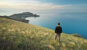 Homem na borda Penhasco da montanha e do mar fotos de stock royalty free