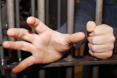 Homem na cadeia que tenta alcangar para fora Fotografia de Stock Royalty Free
