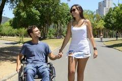 Homem na cadeira de rodas e na amiga Fotos de Stock
