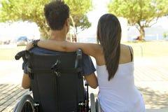 Homem na cadeira de rodas e na amiga foto de stock