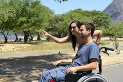 Homem na cadeira de rodas e na amiga imagens de stock