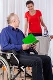 Homem na cadeira de rodas e na enfermeira de ajuda fotos de stock