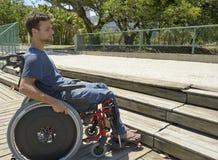 Homem na cadeira de rodas na frente das escadas fotografia de stock