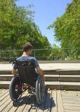 Homem na cadeira de rodas na frente das escadas fotos de stock royalty free
