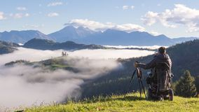 Homem na cadeira de rodas que toma as fotos da paisagem bonita em uma manhã nevoenta, St Thomas Slovenia fotografia de stock royalty free