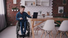 Homem na cadeira de rodas usando o computador moderno em casa vídeos de arquivo