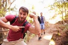 Homem na caminhada com os amigos que fazem o gesto engraçado na câmera Fotos de Stock Royalty Free