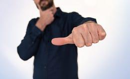 Homem na camisa azul que faz o gesto de mão com polegar lateralmente imagens de stock royalty free