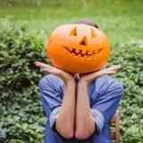 Homem na camisa azul que guarda a abóbora grande na frente de sua cara Halloween feliz foto de stock
