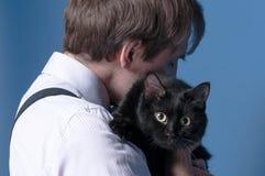 Homem na camisa cor-de-rosa e no suspender que guardam e que abraçam o gato bonito preto fotografia de stock