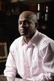 Homem na camisa cor-de-rosa na tabela Imagem de Stock Royalty Free