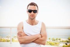 Homem na camisa e nos óculos de sol com mãos do cruzamento Fotos de Stock Royalty Free