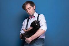 Homem na camisa, no suspender e no laço cor-de-rosa guardando e olhando ao gato preto imagens de stock royalty free