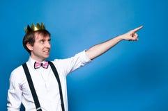Homem na camisa, no suspender, no laço e na coroa dourada, sorrindo, olhando afastado e ponting com o dedo na distância no fund foto de stock royalty free