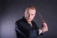 Homem na camisa preta com a espada tradicional do katana Com espaço da cópia Imagens de Stock Royalty Free