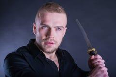Homem na camisa preta com a espada tradicional do katana Com espaço da cópia Foto de Stock Royalty Free