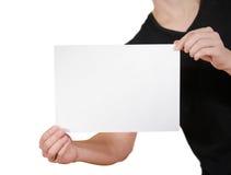 Homem na camisa preta de t que guarda o papel vazio do branco A4 Folheto prese Imagens de Stock
