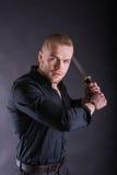 Homem na camisa preta que guarda a espada do katana que olha a câmera contra o fundo da parede Fotografia de Stock Royalty Free