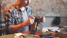 Homem na camisa verificada que costura o artigo de couro video estoque