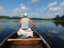Homem na canoa no lago azul imagens de stock royalty free