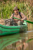 Homem na canoa velha no rio com trouxa e chapéu Foto de Stock Royalty Free
