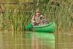 Homem na canoa velha no rio com trouxa e chapéu na frente da ponte de madeira velha Fotografia de Stock Royalty Free