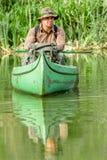 Homem na canoa velha no rio com trouxa e chapéu - natureza bonita Imagens de Stock Royalty Free