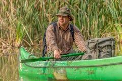 Homem na canoa velha no rio com trouxa e chapéu - retrato Fotografia de Stock Royalty Free