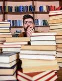 Homem na cara chocada entre pilhas dos livros na biblioteca, estantes no fundo Conceito científico da descoberta professor imagens de stock royalty free