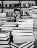 Homem na cara chocada entre pilhas dos livros na biblioteca, estantes no fundo Conceito científico da descoberta professor foto de stock
