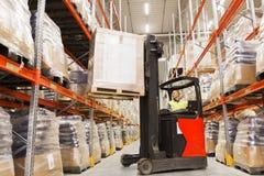 Homem na carga da carga da empilhadeira no armazém Foto de Stock