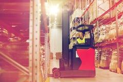 Homem na carga da carga da empilhadeira no armazém Imagem de Stock