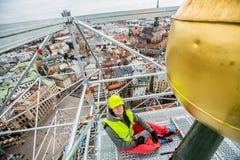 Homem na cidade, igreja alta do trabalhador de Highclimber fotografia de stock royalty free