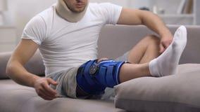 Homem na cinta de joelho de fixação do neopreno do colar cervical da espuma e encontro no sofá, reabilitação video estoque