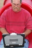 Homem na corrediça vermelha usando o portátil Imagens de Stock