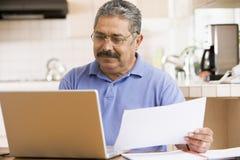Homem na cozinha com portátil e documento imagens de stock