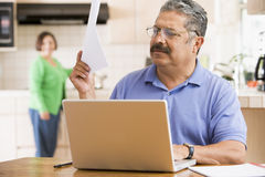 Homem na cozinha com portátil e documento imagem de stock royalty free